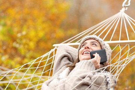 Happy woman lying on hammock talking on smart phone in autumn season in a forest Stok Fotoğraf