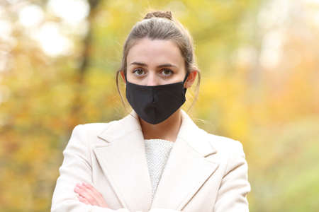 Serious woman posing in autumn with mask due covid 19 in a park in winter Stok Fotoğraf