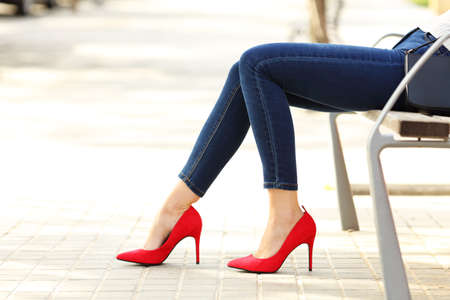 Side view portrait of a beauty woman legs with jeans and high heels sitting in a bench Standard-Bild