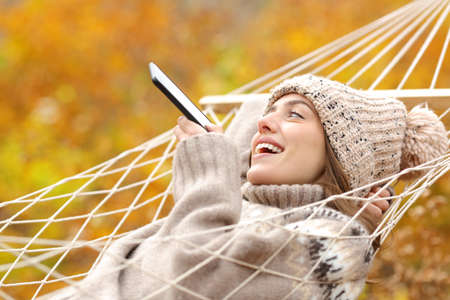 Happy lady lying on hammock dictating message on smart phone in fall season