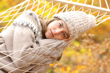 Beauty woman resting on hammock in autumn season looking at camera in a forest Stok Fotoğraf