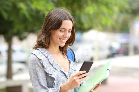 Happy student checks smart phone walking in the street