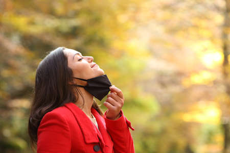 Profile of a woman taking off protective mask to breath fresh air in a park in covid times