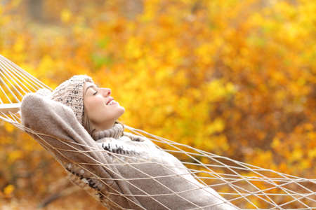 Profile of a happy woman lying on a rope hammock in fall season in a forest