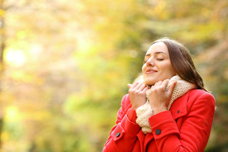 Beauty woman in red jacket heating grabbing scarf in a park in autumn Standard-Bild