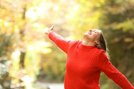 Excited woman in red celebrating vacation standing in a forest in autumn