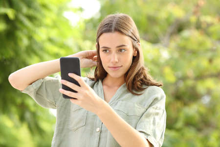 Woman combing hair using smartphone as a mirror in a park