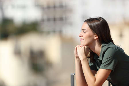 Satisfied woman contemplating views from balcony in a town a sunny summer day Stok Fotoğraf
