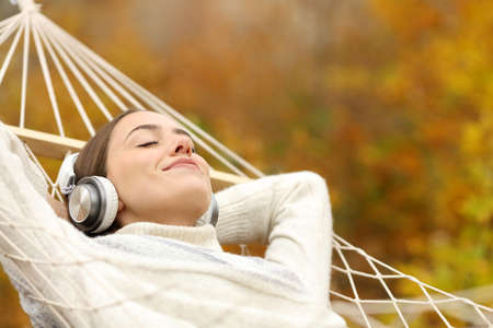 Relaxed woman listening to music with headphones lying on hammock in autumn in a forest