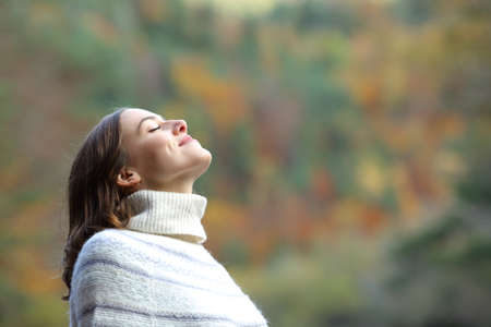 Side view portrait of a satisfied woman breathing fresh air in the mountain in winter
