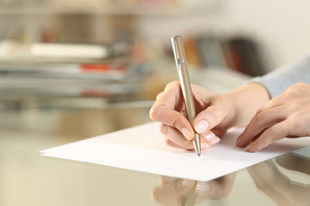 Close up of woman hands writing letter on paper sheet on glass table at home