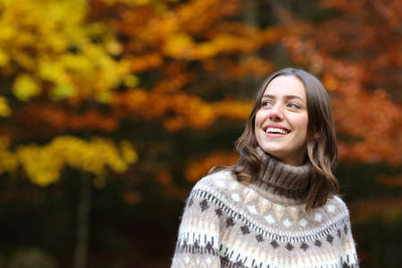 Happy woman in a park in autumn season looking at side