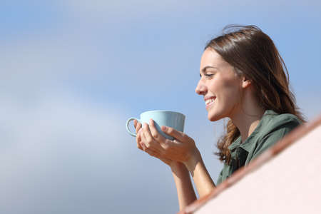 Side view portrait of a happy woman contemplating views from apartment balcony drinking coffee