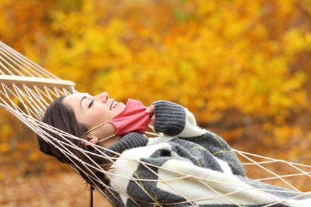 Profile of a happy woman taking off protective mask breathing fresh air on hammock in autumn