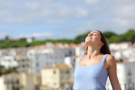 Satisfied woman relaxing breathing fresh air in a rural town Stok Fotoğraf