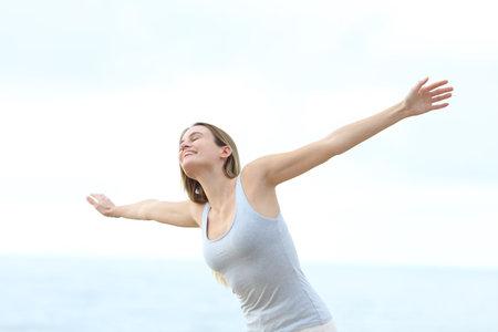 Happy teen enjoying stretching arms on the beach Stok Fotoğraf