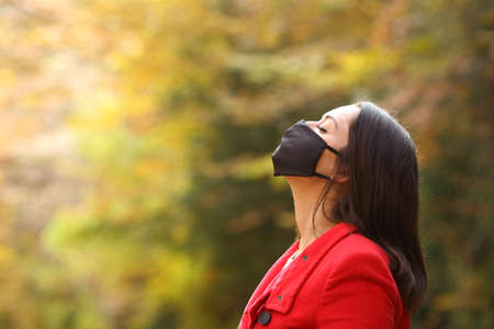 Side view portrait of a woman in red breathing fresh air with mask in a forest in covid times