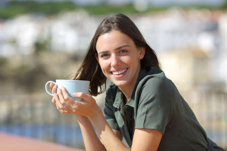 Happy woman looks at camera holding coffee cup in a hotel balcony on the beach