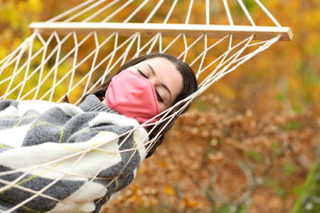 Woman with mask due covid 19 sleeping lying on hammock in autumn