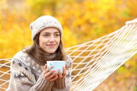 Happy woman contemplating views holding coffee mug sitting on hammock in autumn holidays Stok Fotoğraf