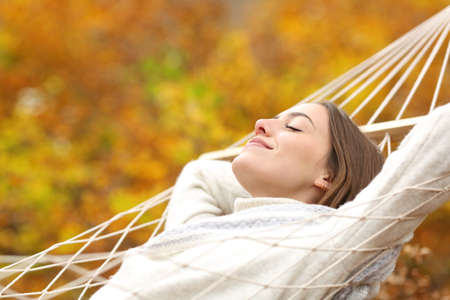Relaxed woman resting on hammock in fall season in autumn in a forest