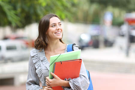 Happy student walking towards camera looking at side in the street