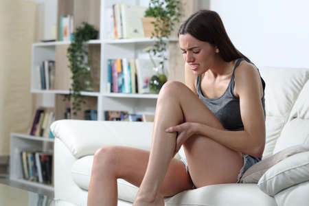 Stressed woman suffering a cramp in the calf muscle sitting on a couch at home