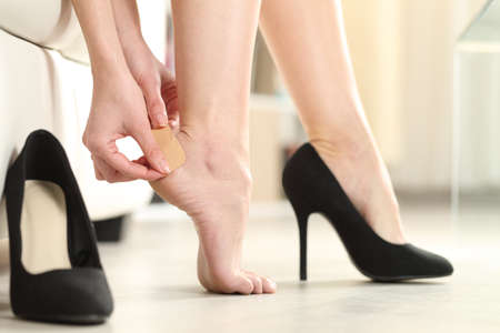 Close up of a woman foot in highheels putting a plaster on her heel at home Stockfoto