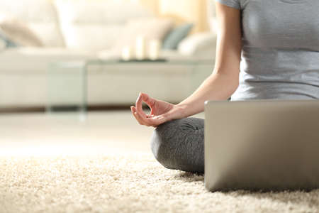Front view close up portrait of a female hand doing yoga exercise watching tutorial on laptop on the floor at home Stok Fotoğraf