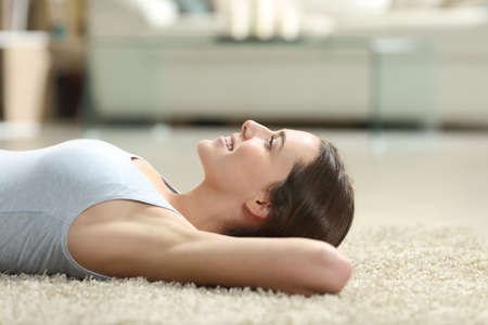 Side view portrait of a happy woman relaxing with waxed armpit lying on a carpet at home