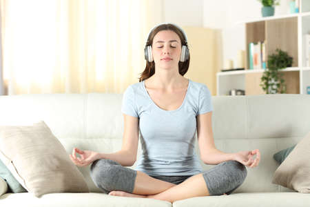 Front view of a woman with headphones listening tutorial meditating doing yoga on a couch at home Stok Fotoğraf