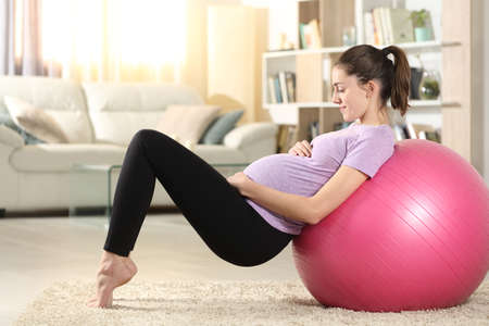 Side view portrait of a happy pregnant woman doing exercise at home with a ball at home