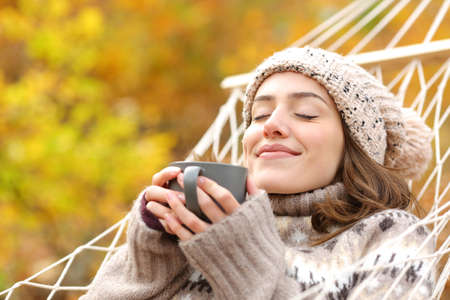 Relaxed woman smelling coffee lying on hammock in autumn holidays