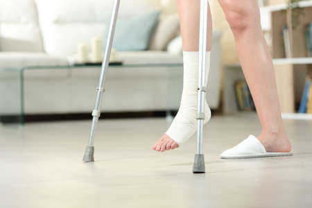 Side view portrait of a disabled woman with bandaged foot walking with crutches at home