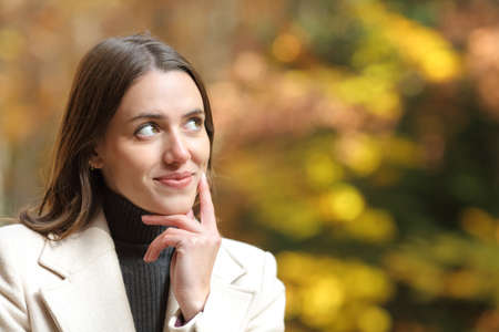 Portrait of a satisfied woman looking at side in a park in autumn season