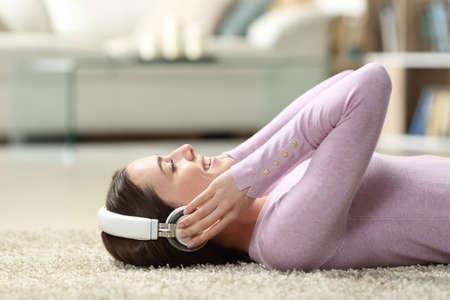 Side view of a woman wearing headphones listening to music lying on a carpet at home