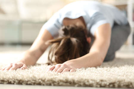 Woman doing yoga child pose on a carpet in the living room at home