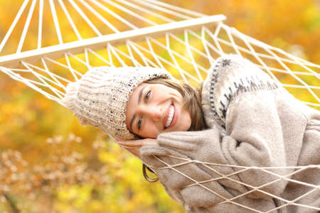 Happy woman with perfect smile resting on hammock looking at camera in autumn in a forest