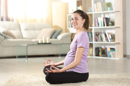 Happy pregnant woman doing yoga exercise at home looking at you Stok Fotoğraf