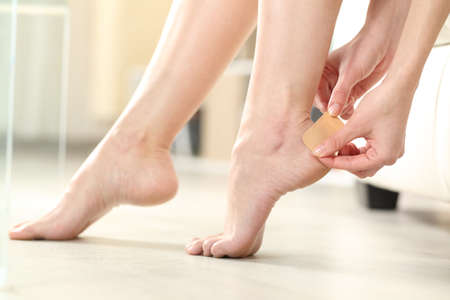 Profile of a woman hands putting stiking plaster on barefoot heel at home