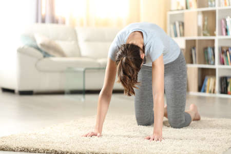 Woman practicing yoga cat pose on the floor at home