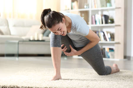 Woman suffering cramp practicing yoga exercise on the floor at home Stok Fotoğraf