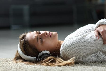 Sad woman listening to music wearing headphones lying on the floor at home Foto de archivo