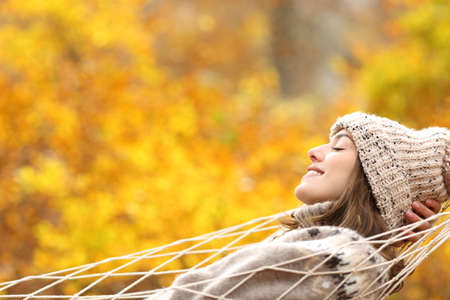 Side view portrait of a happy woman relaxing lying on a hammock in autumn in a forest