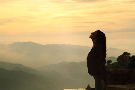Side view portrait of a woman silhouette breathing fresh air in the mountain at sunset