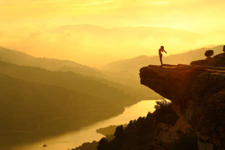 Woman silhouette breathing fresh air in the top of a cliff in the mountain at sunset with a beautiful landscape in the background