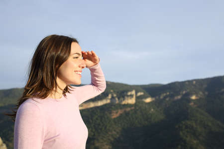 Profile of a happy woman looking forward with hand on forehead contemplating views in the mountain