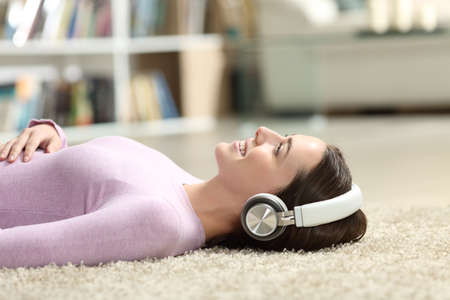 Happy woman listening to music lying on a carpet at home