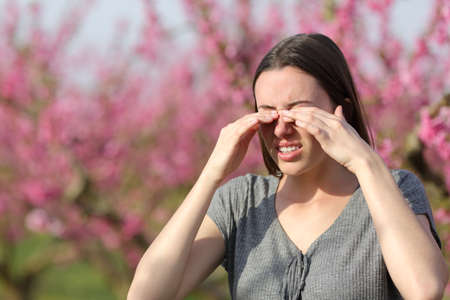 Stressed woman scratching itchy eyes in springtime in a pink flowers field