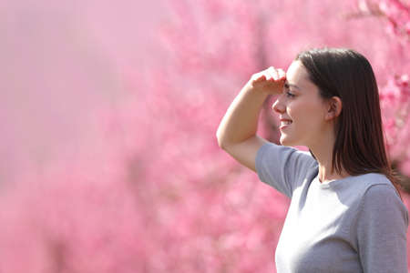 Side view portrait of a happy woman searching looking away protecting from sun with her hand in a pink flowered field Stockfoto